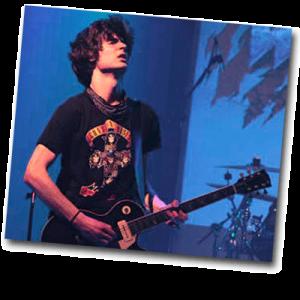 Adolescent garçon jouant de la guitare en concert