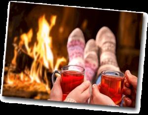 Couple buvant des boissons chaudes près du feu de cheminé en hiver