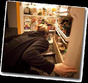 Femme fouillant dans le frigo en pleine nuit