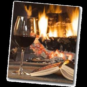 Verre de vin et livre devant un feu de cheminée le soir