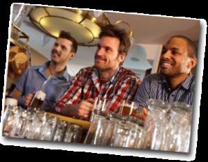 Hommes assis à un bar buvant un verre de bière